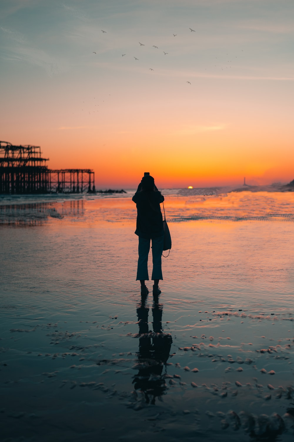 silhouette of woman standing on beach during sunset