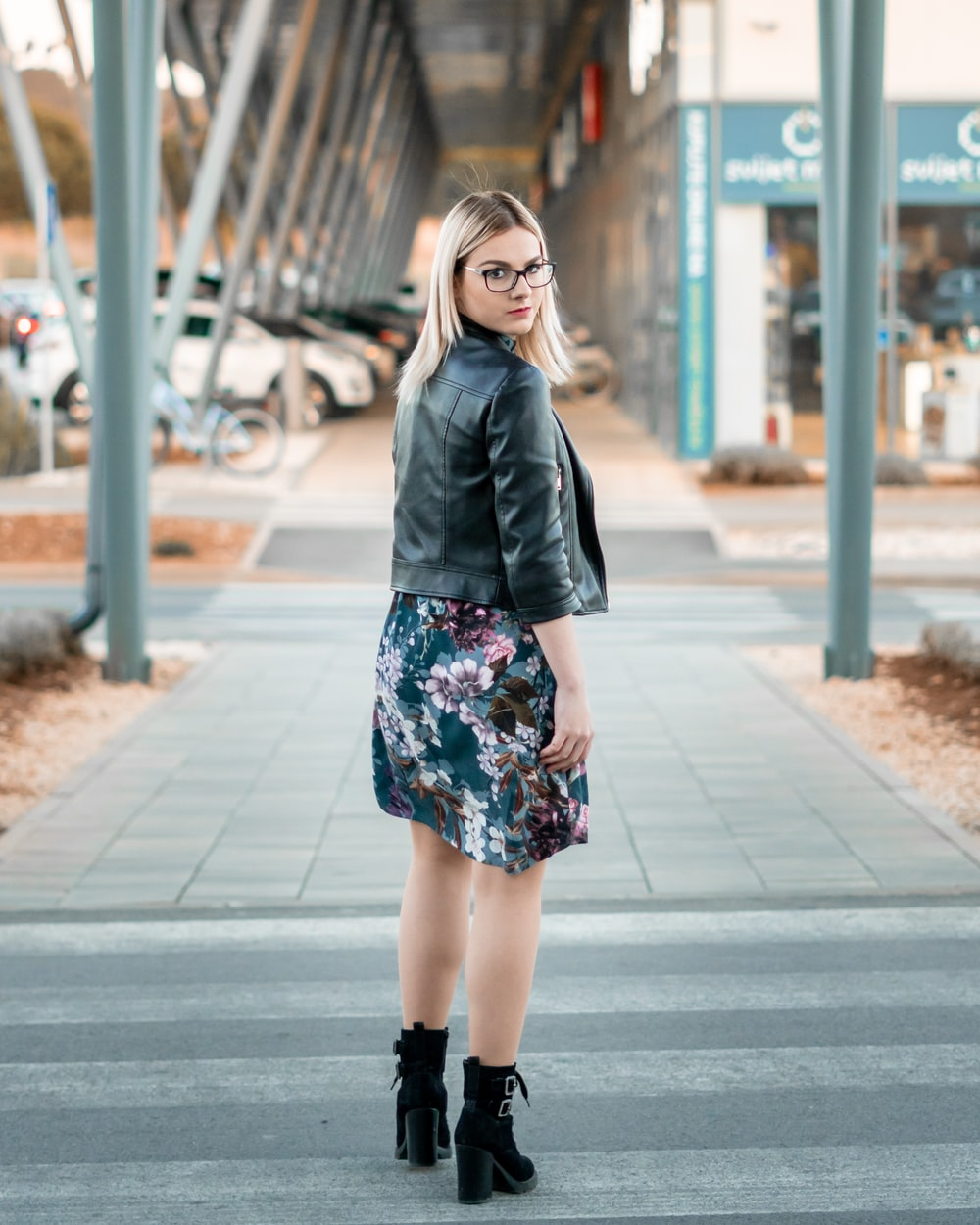 woman in black leather jacket standing on sidewalk during daytime