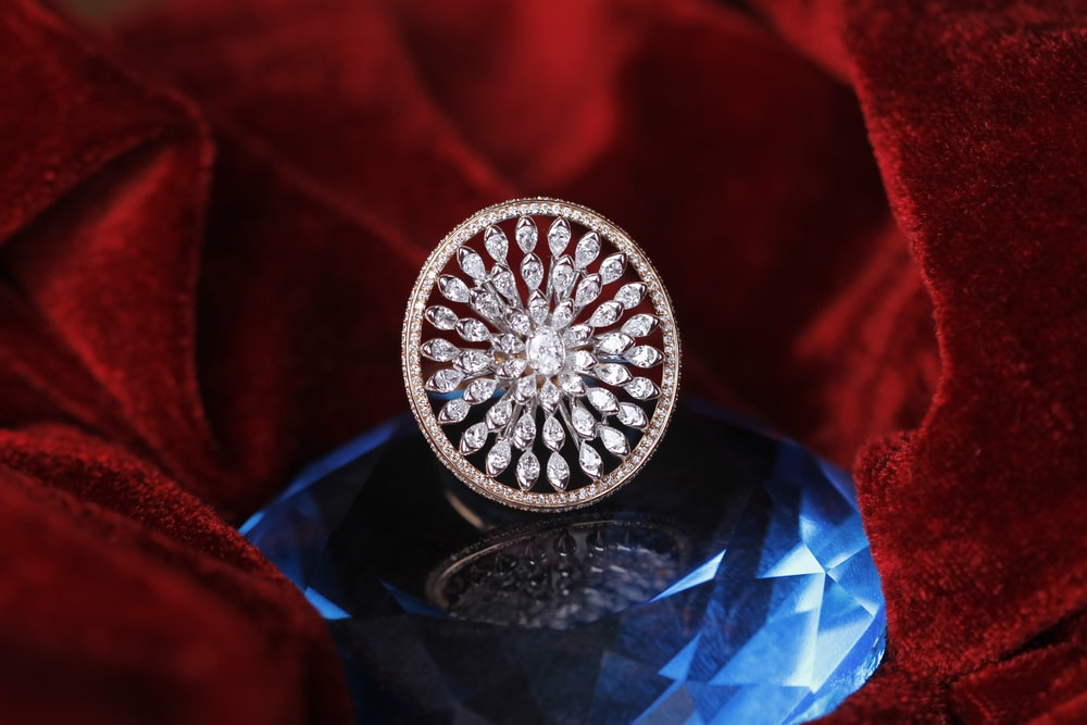 silver diamond studded ring on red textile