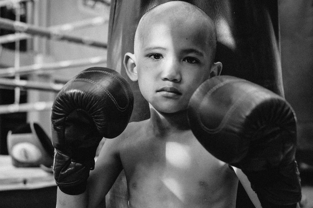 topless boy holding black boxing gloves
