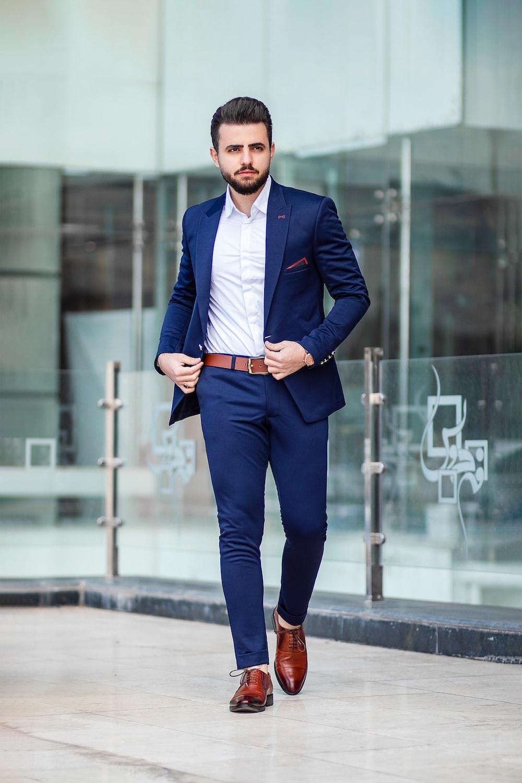 man in blue suit standing on sidewalk during daytime