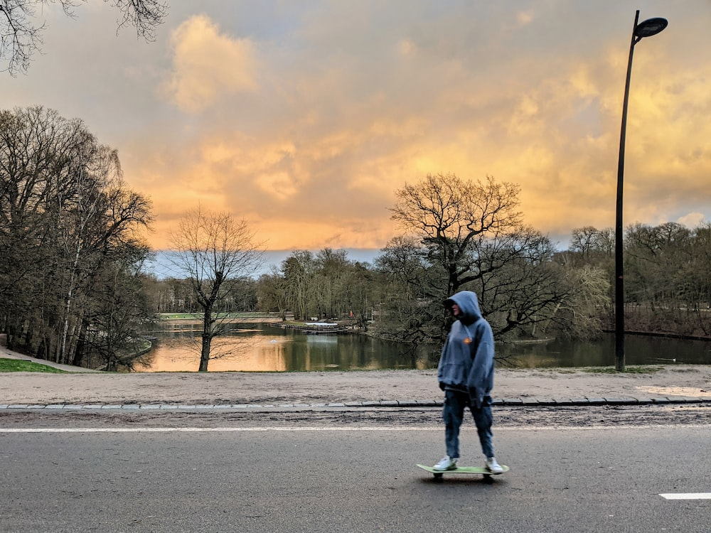 man in blue jacket standing on gray concrete road near body of water during daytime