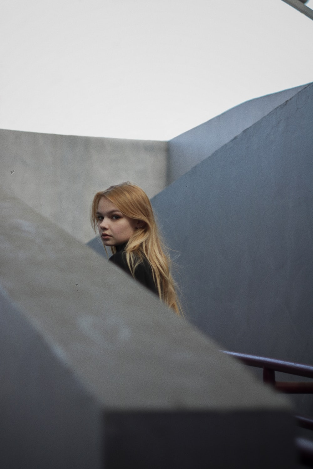 woman in black long sleeve shirt leaning on gray concrete wall during daytime