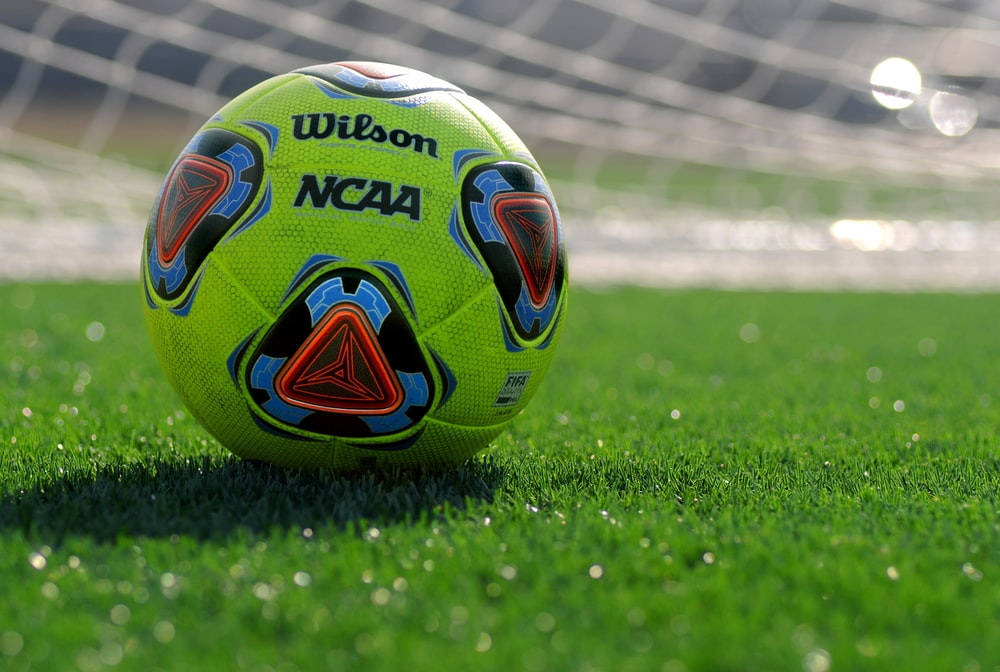 white green and blue soccer ball on green grass field during daytime