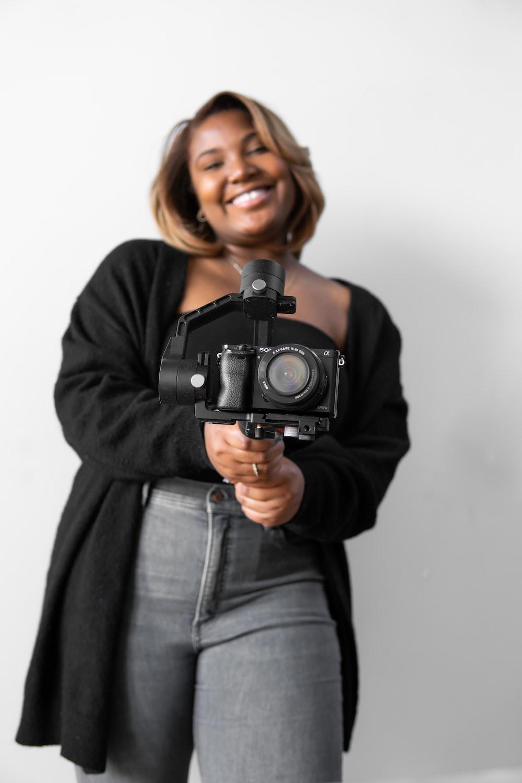 woman in black jacket holding black dslr camera