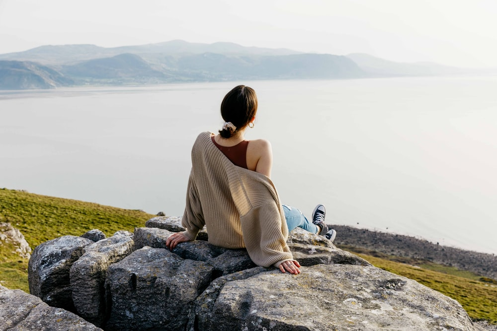 woman in brown long sleeve shirt sitting on rock near body of water during daytime