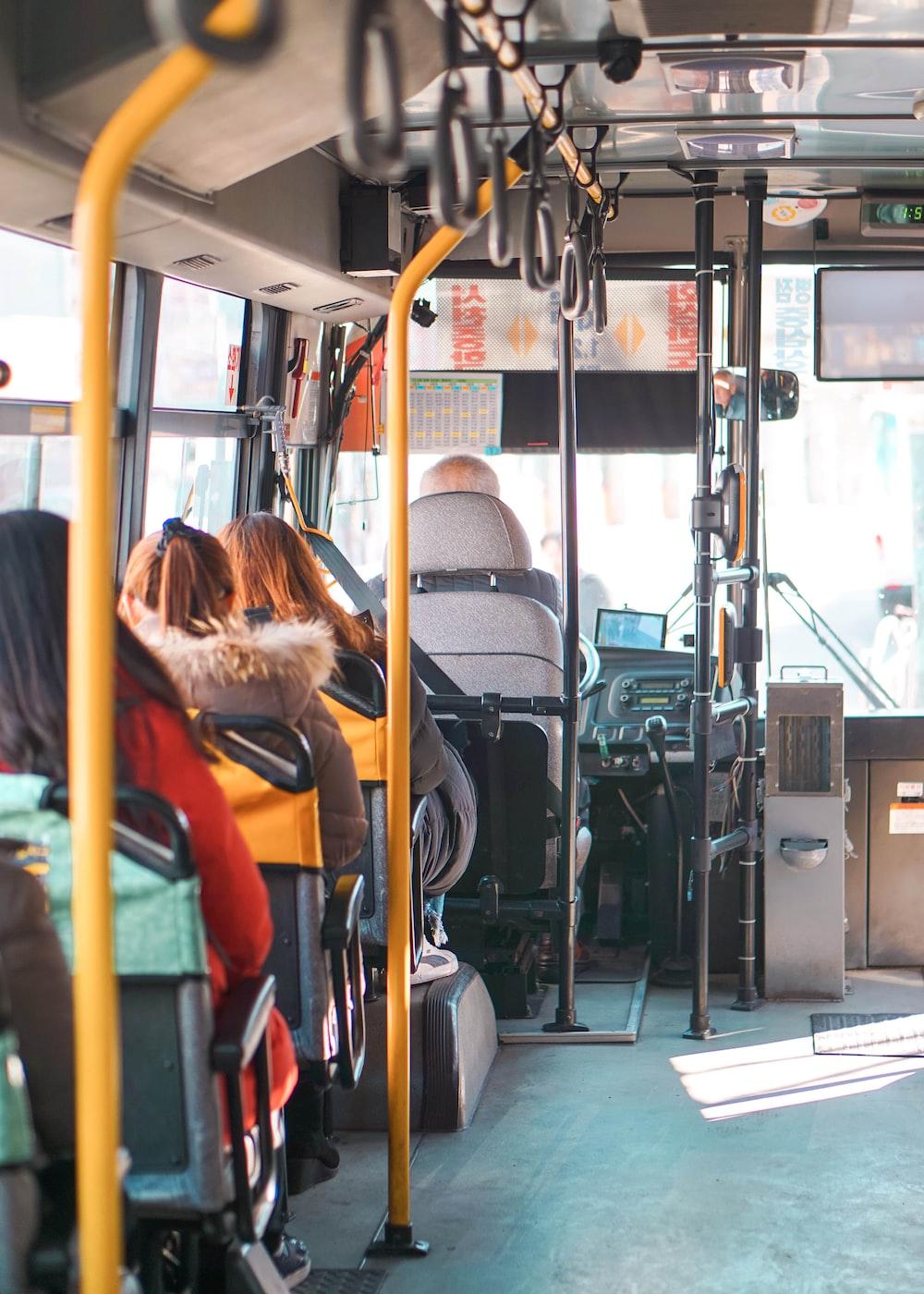 woman in orange jacket sitting on bus seat
