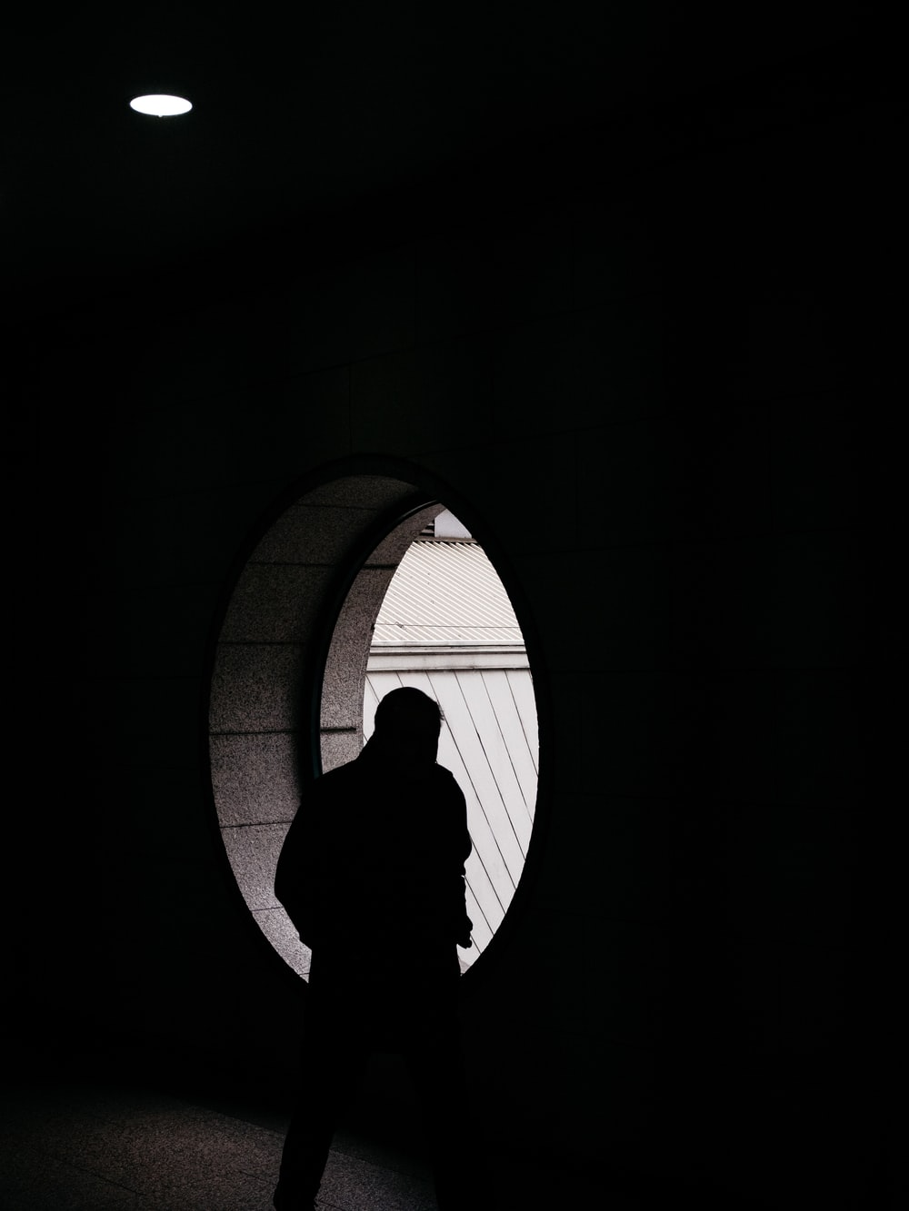 silhouette of person standing in front of window