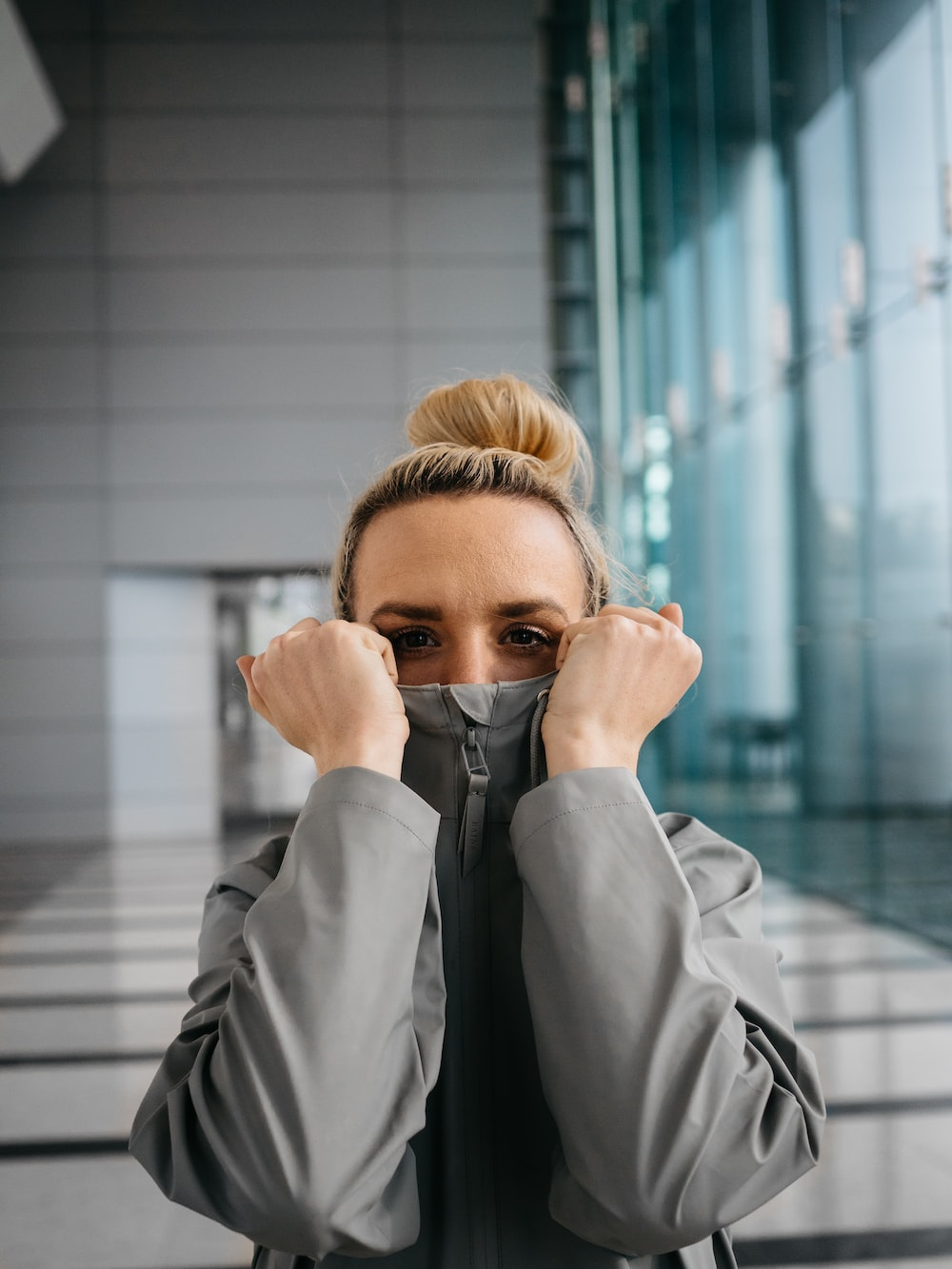 woman in gray coat covering her face with her hand