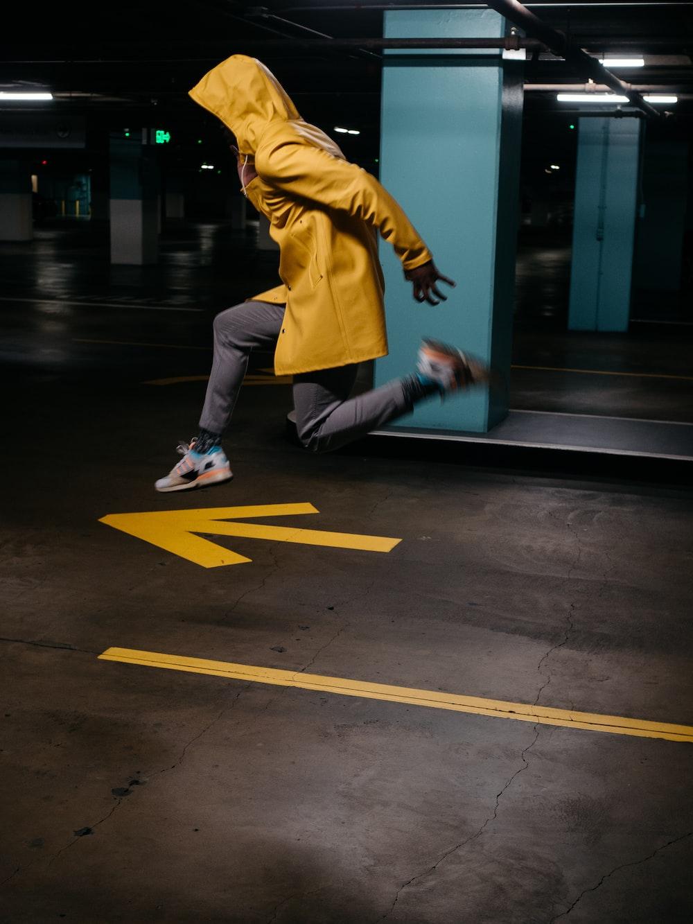 man in yellow long sleeve shirt and white pants walking on sidewalk