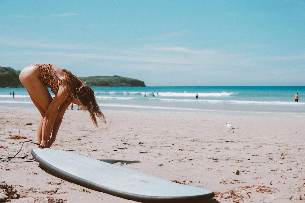 woman in brown bikini walking on beach during daytime