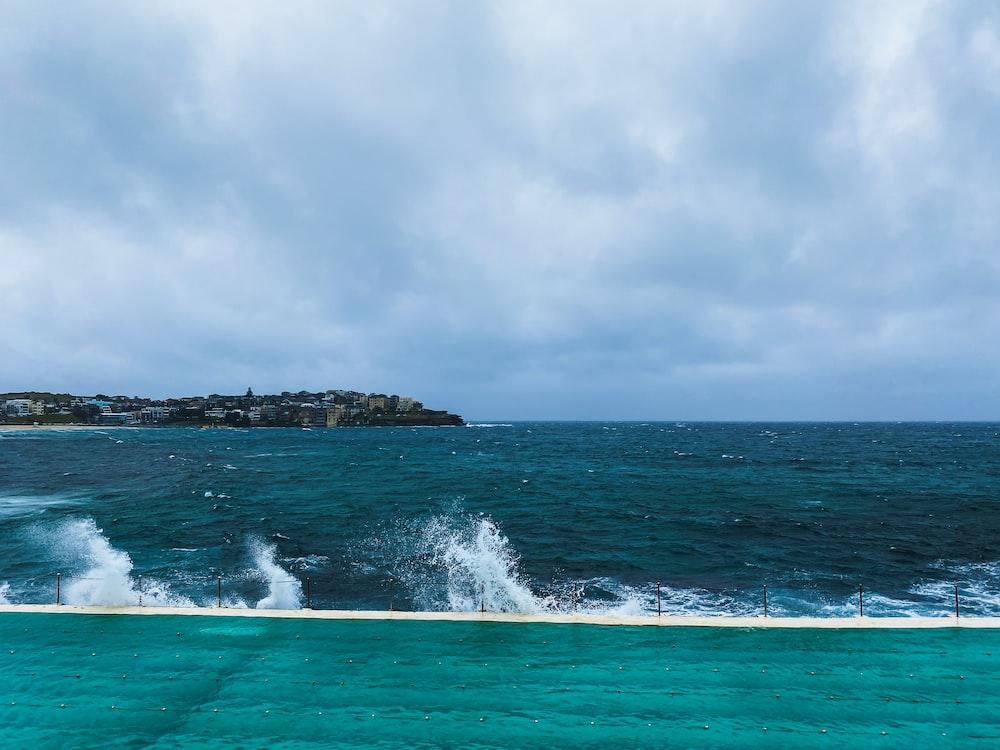 ocean waves crashing on rock formation under white clouds during daytime