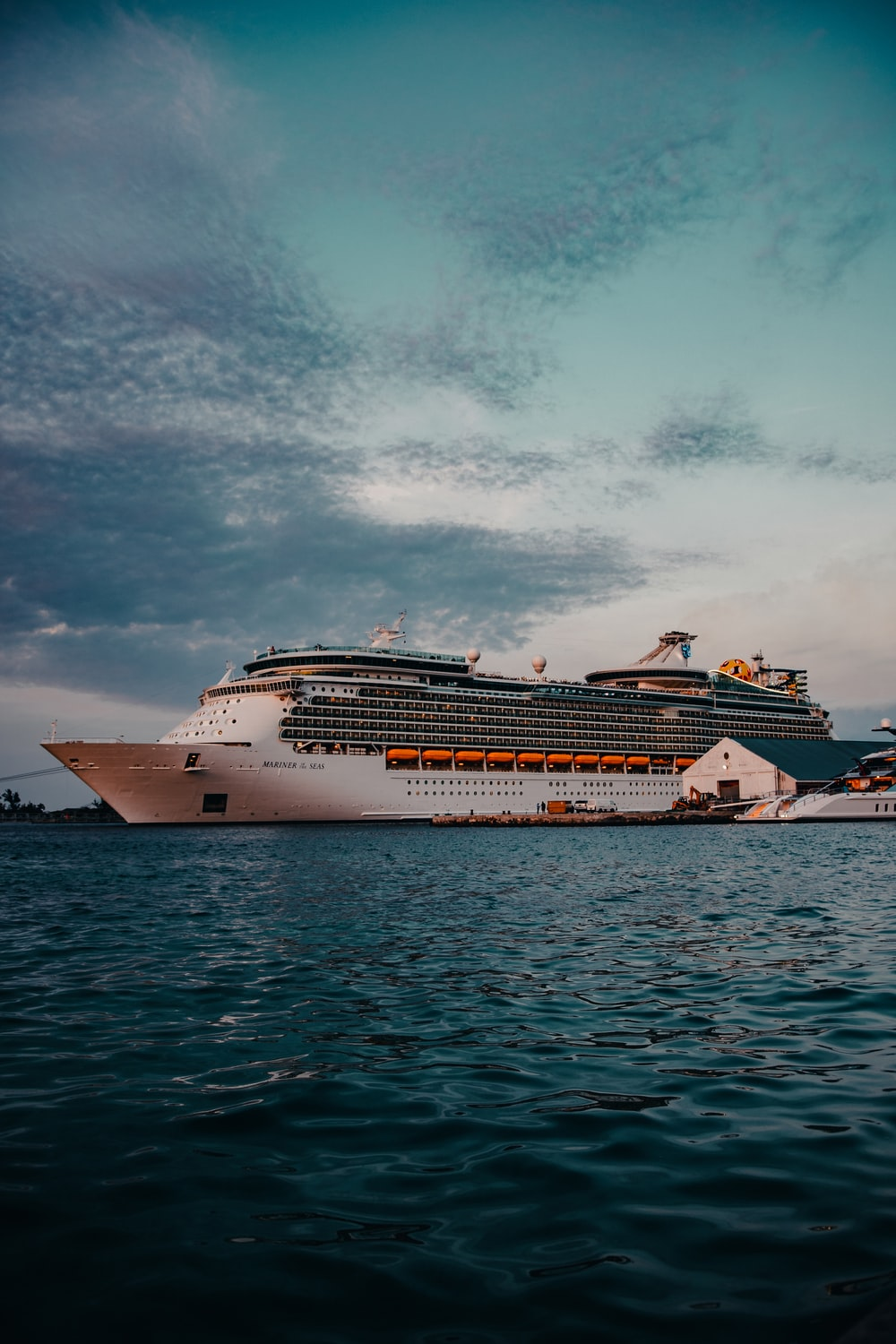 white cruise ship on sea under white clouds and blue sky during daytime