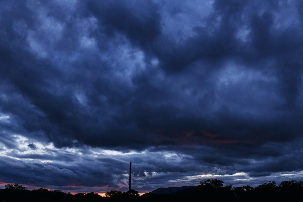 silhouette of mountain under dark clouds