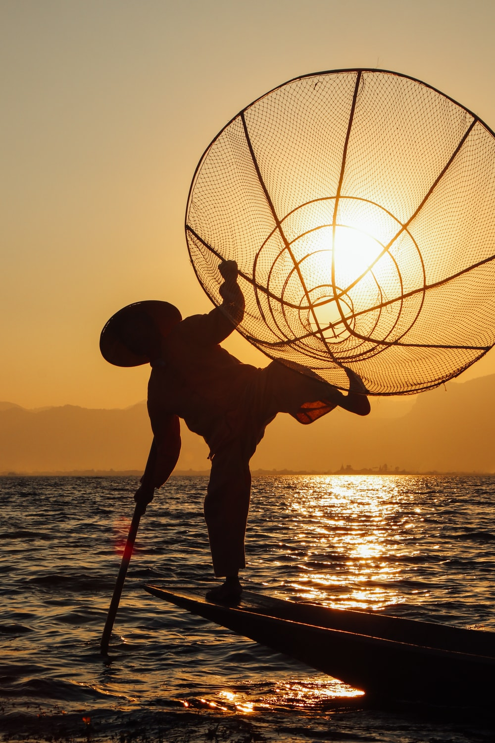 silhouette of man holding basketball during sunset