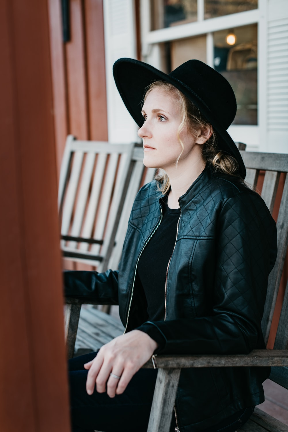 woman in black leather jacket and black hat sitting on brown wooden chair