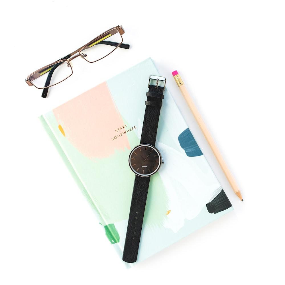 black framed eyeglasses beside blue and pink book
