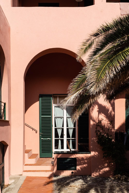 green palm tree beside beige concrete building