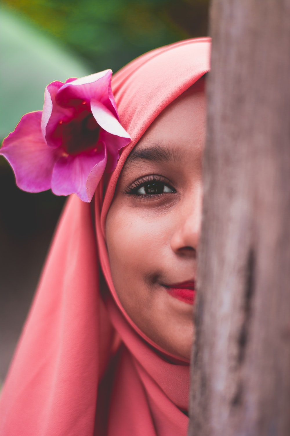 woman in pink hijab and red lipstick
