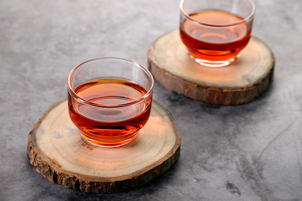 clear glass cup with red liquid on brown wooden table