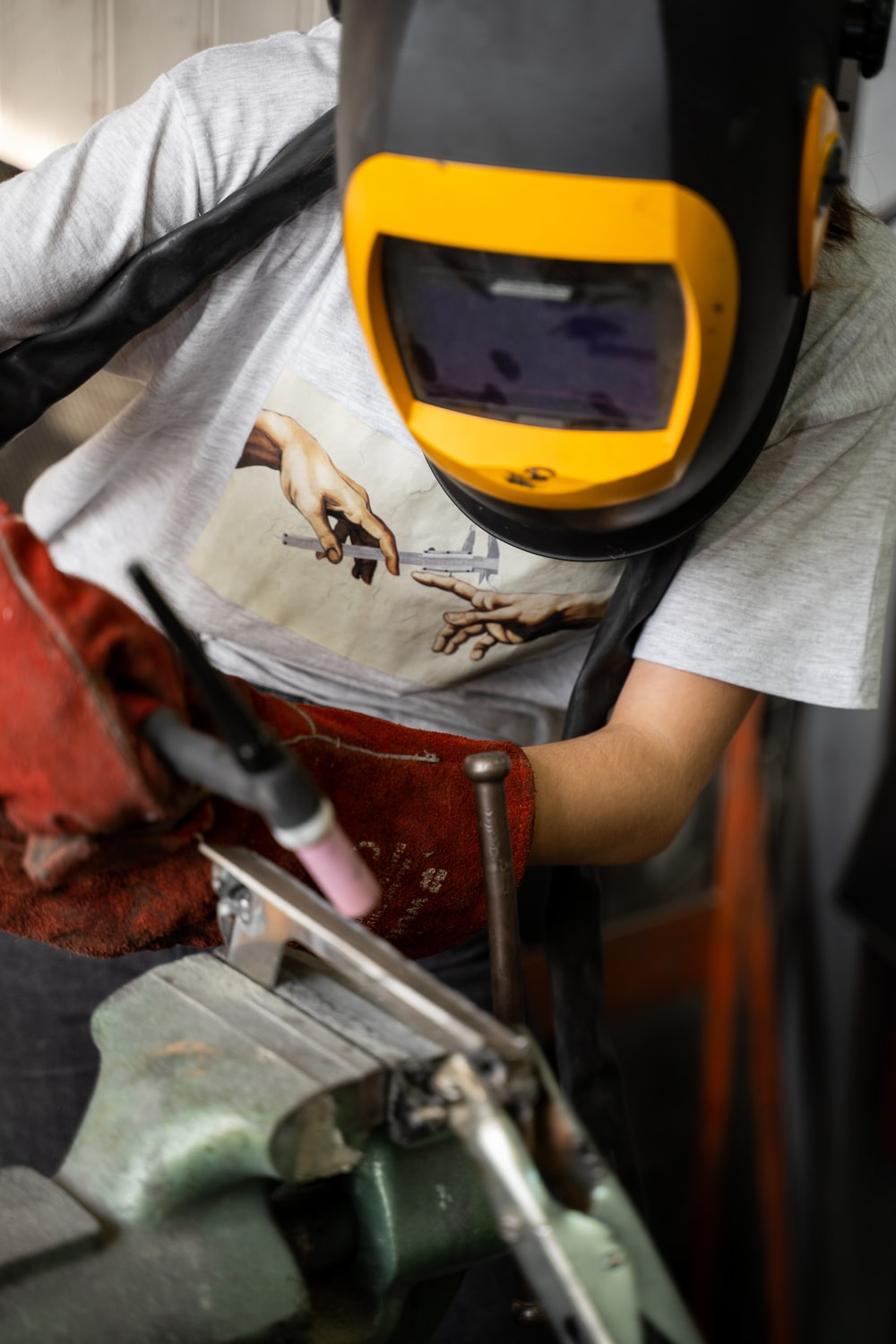 person in white t-shirt holding brown and gray metal tool