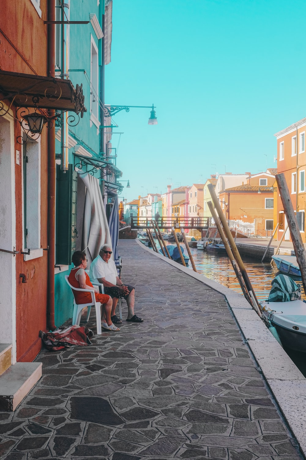 man in blue shirt sitting on chair near blue boat during daytime