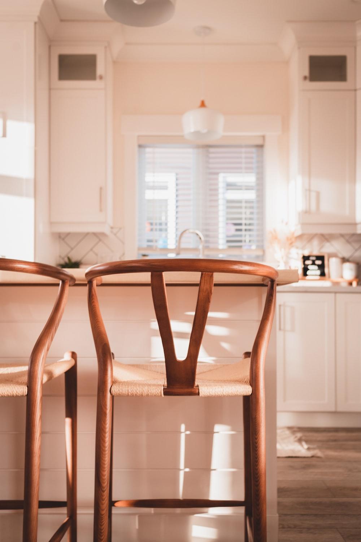 brown wooden chair near white wooden kitchen cabinet