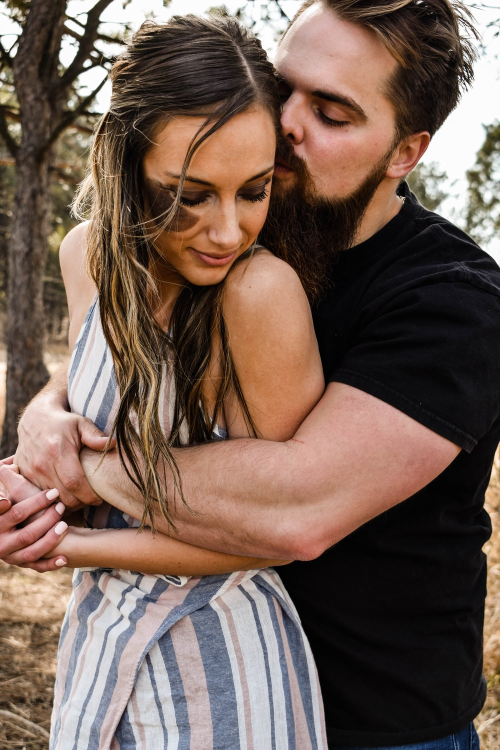 man in black t-shirt kissing woman in white and blue plaid dress