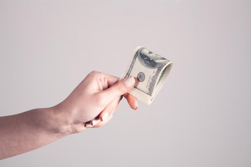 person holding 1 us dollar bill