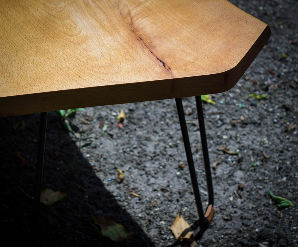 brown wooden table near green plants