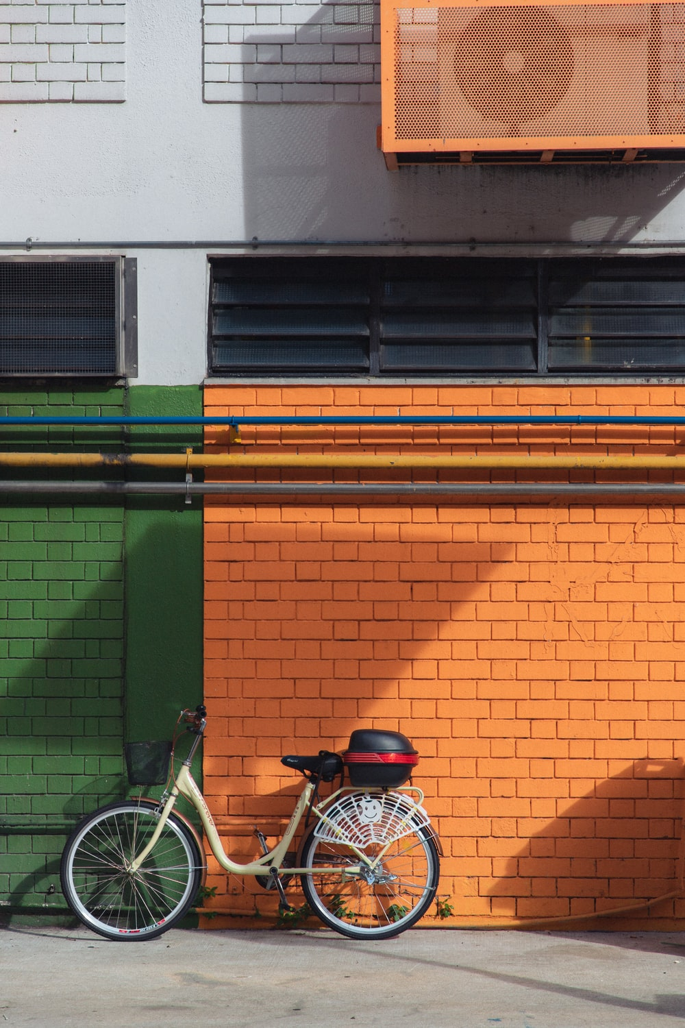 blue and white commuter bike parked beside green and brown concrete building