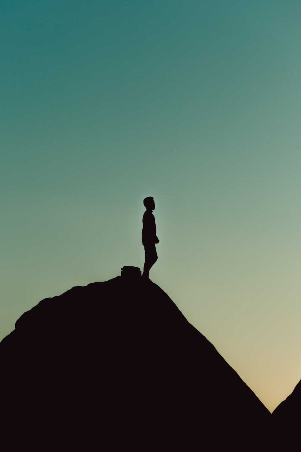 silhouette of man standing on rock formation during daytime