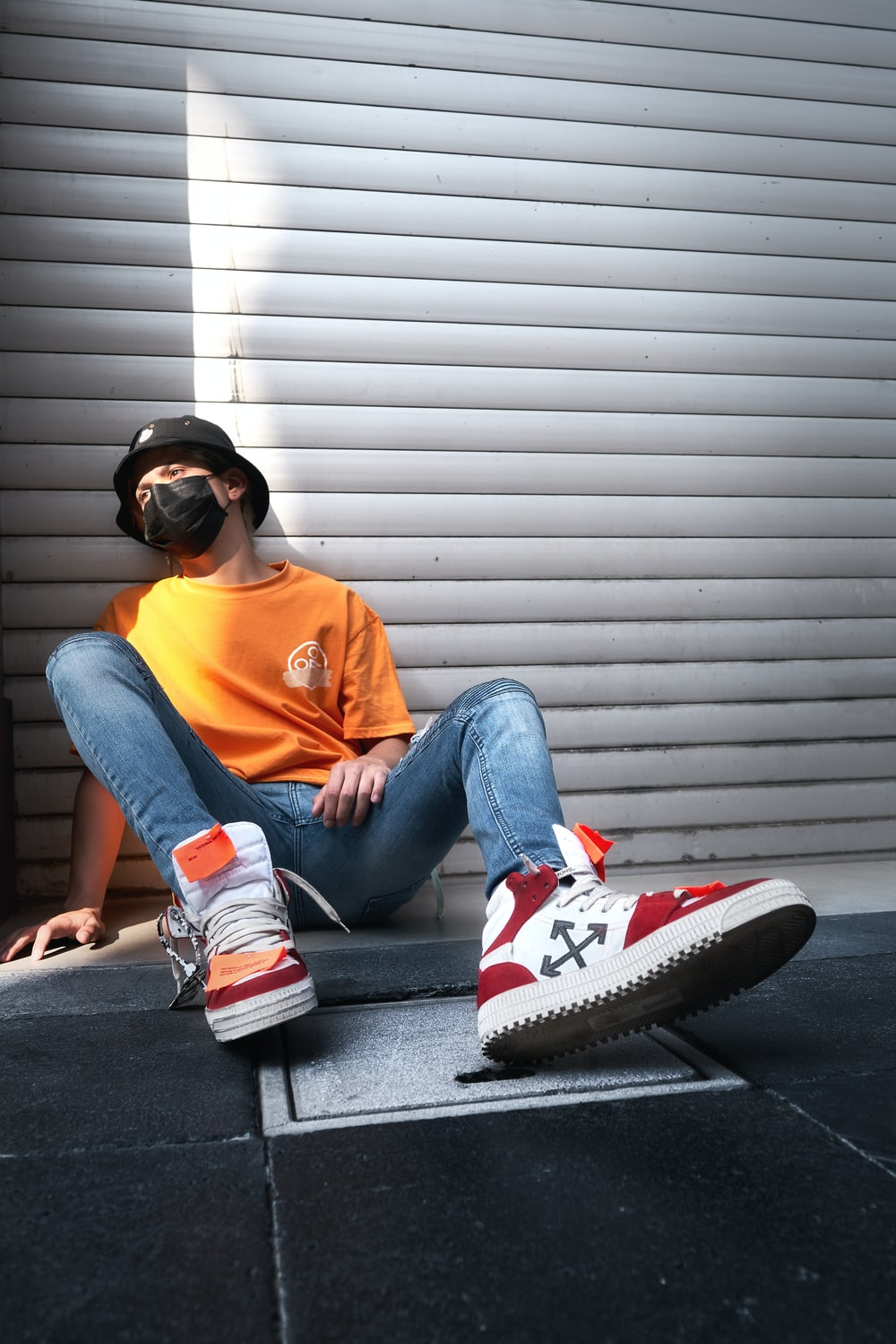 woman in orange crew neck t-shirt and blue denim jeans sitting on gray concrete stairs