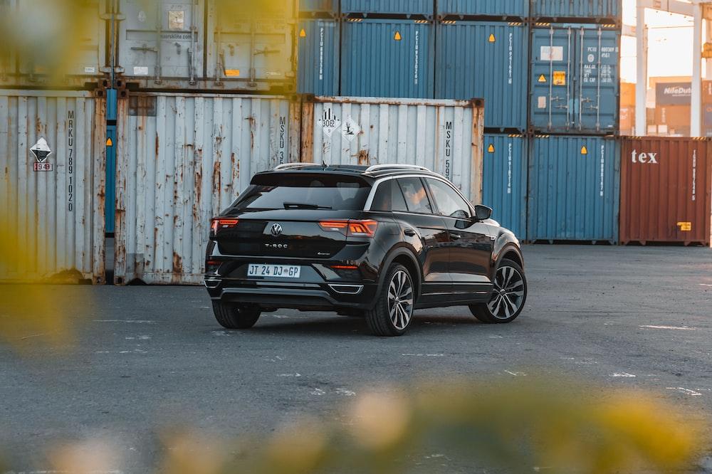 black bmw m 3 parked beside blue steel wall