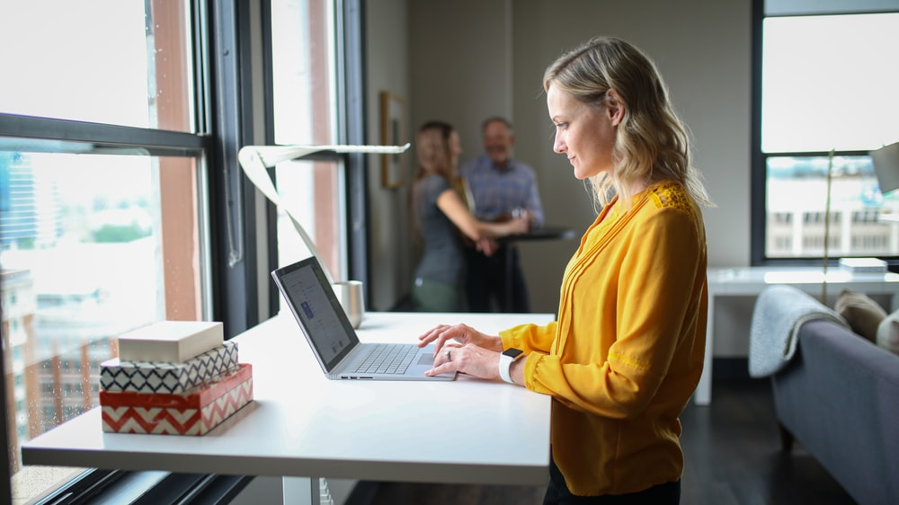 woman in yellow long sleeve shirt using macbook pro