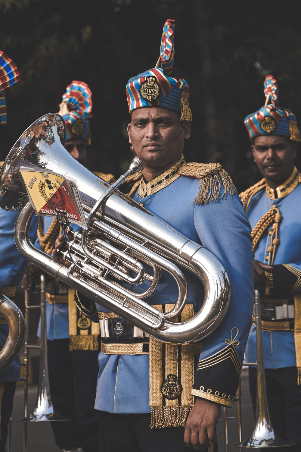 man in gold and blue hat playing trumpet