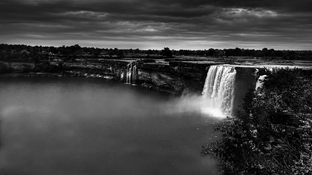 grayscale photo of waterfalls under cloudy sky