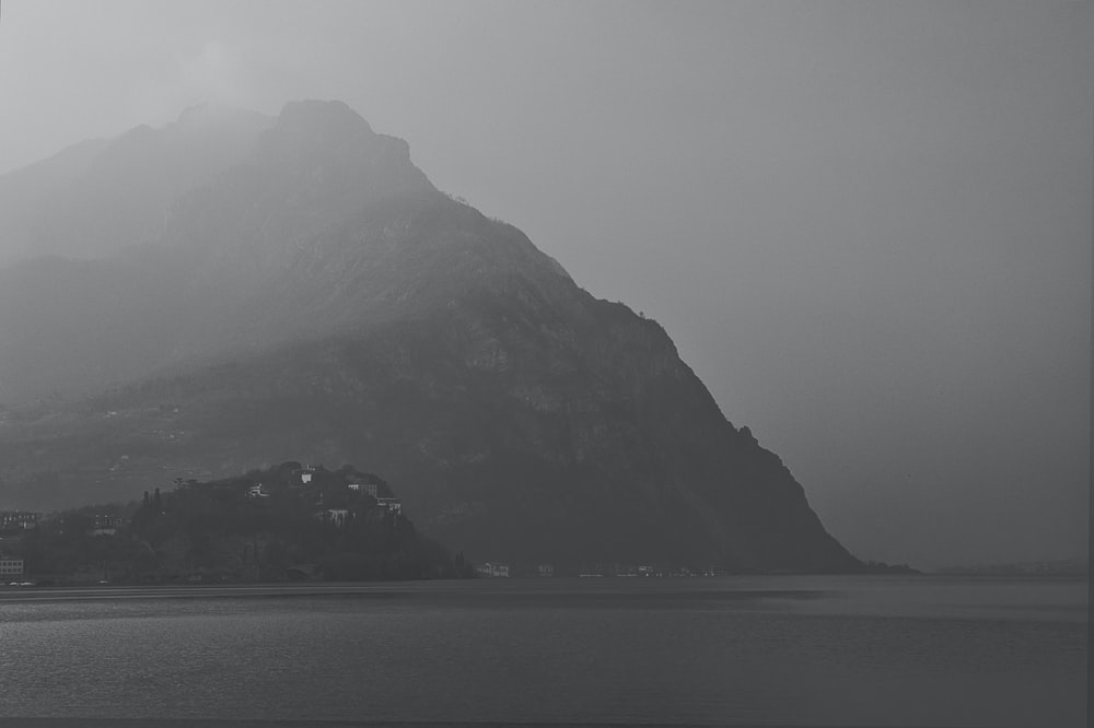 body of water near mountain during foggy weather