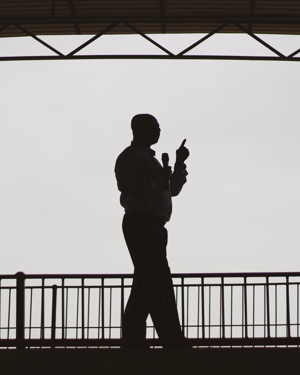 silhouette of man standing near fence during daytime