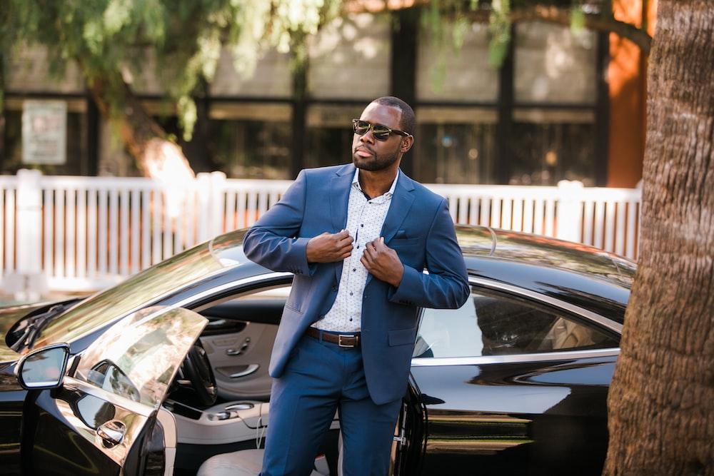 man in blue suit standing beside black car