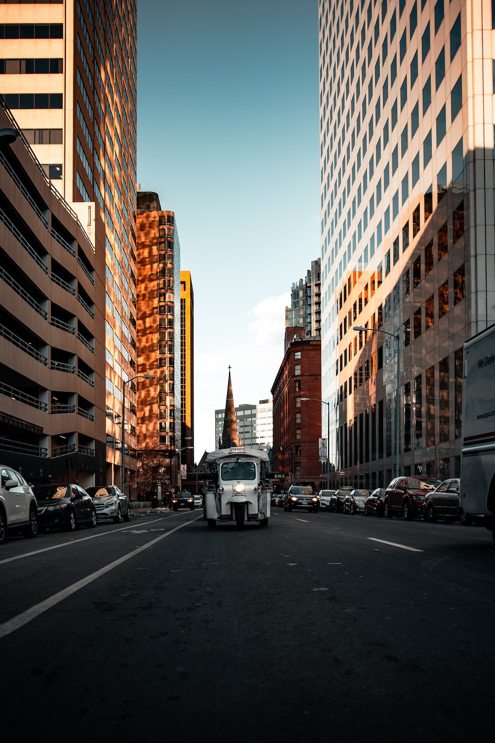 cars on road in between high rise buildings during daytime