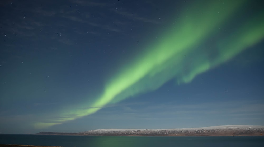 green aurora lights over the sea during night time