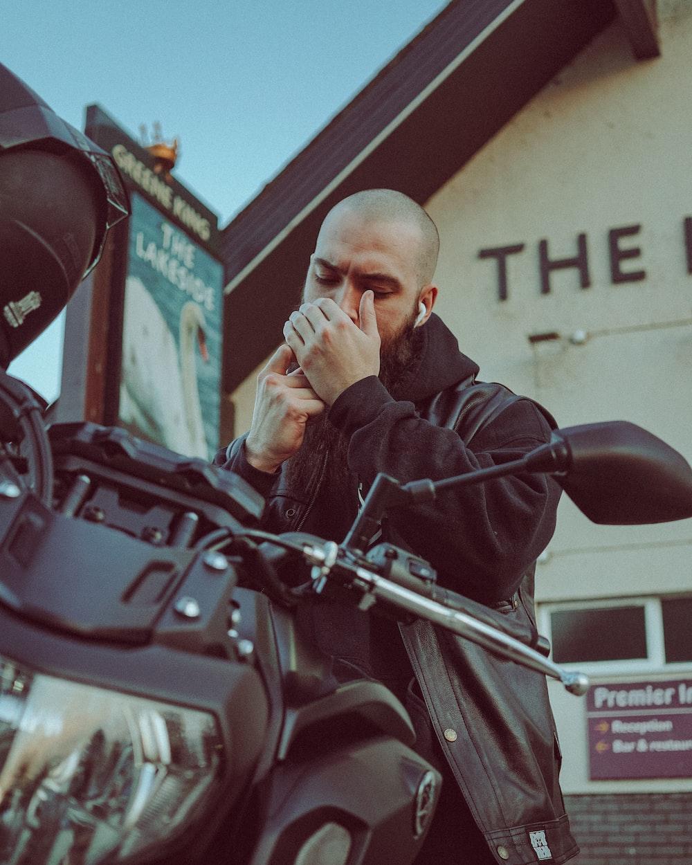 man in black jacket sitting on red motorcycle