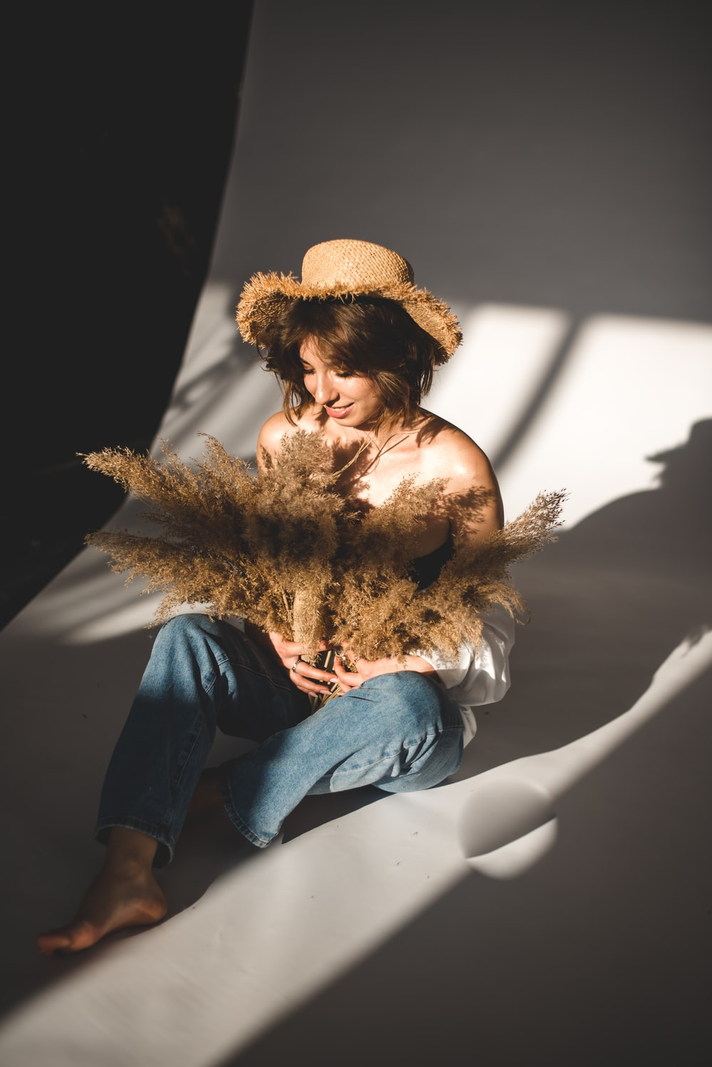 woman in blue denim jeans wearing brown sun hat sitting on white chair