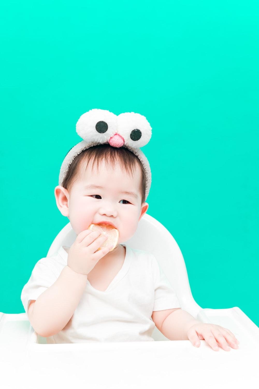 baby in white long sleeve shirt and white and black polka dot headband