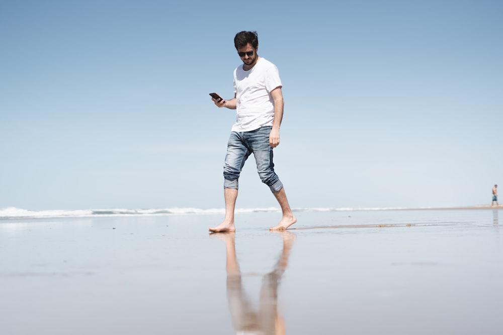 man in white t-shirt and blue denim shorts running on beach during daytime