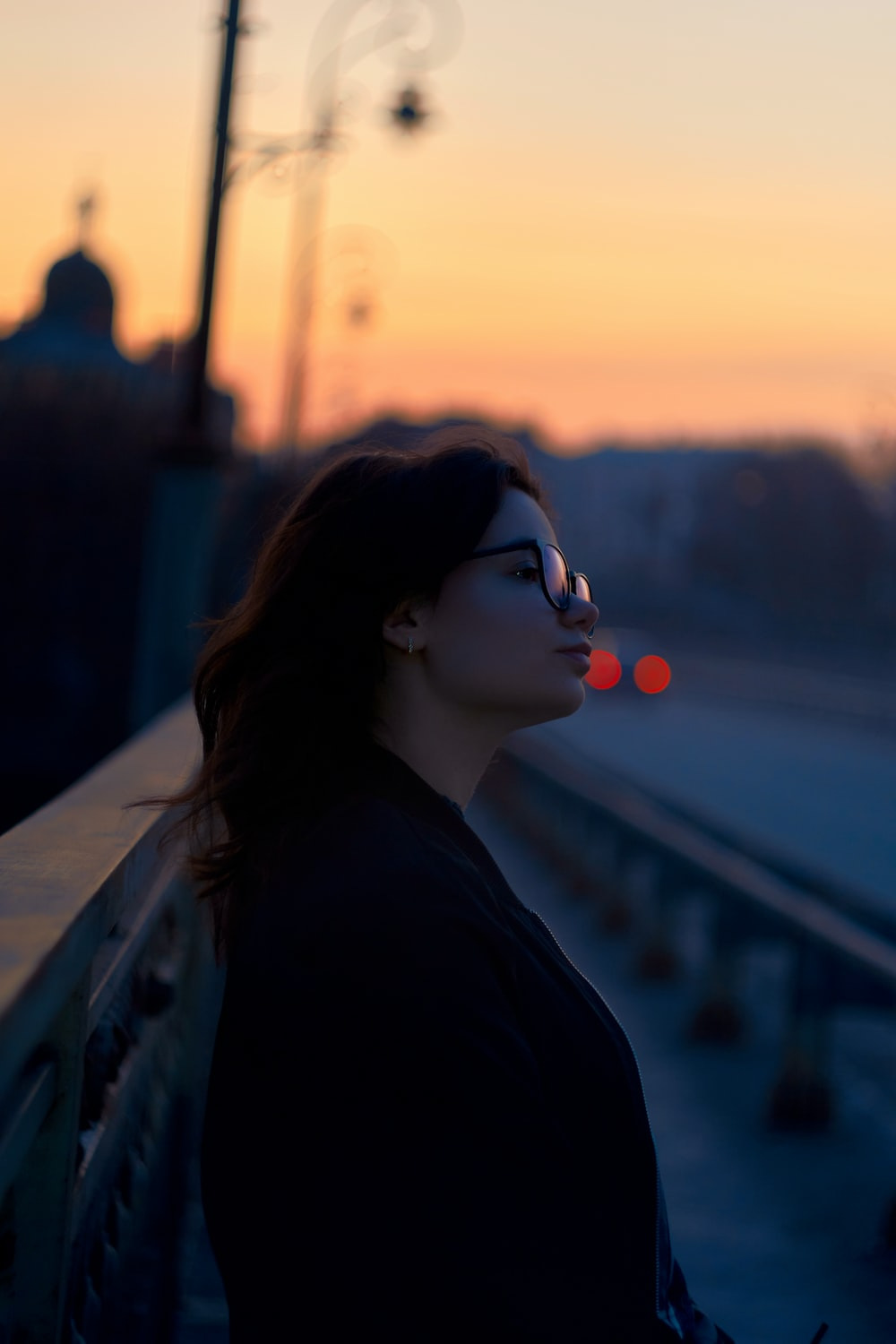 woman in black jacket wearing sunglasses during sunset