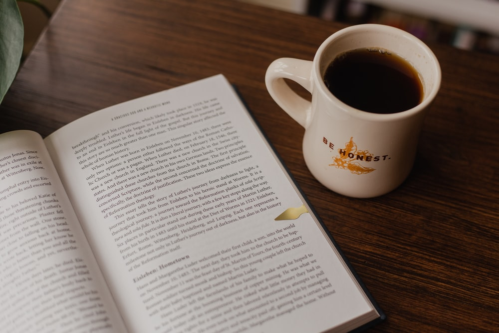 white book beside white ceramic mug on brown wooden table