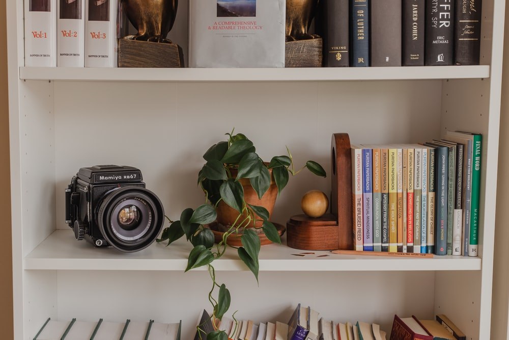 black nikon camera on white wooden shelf