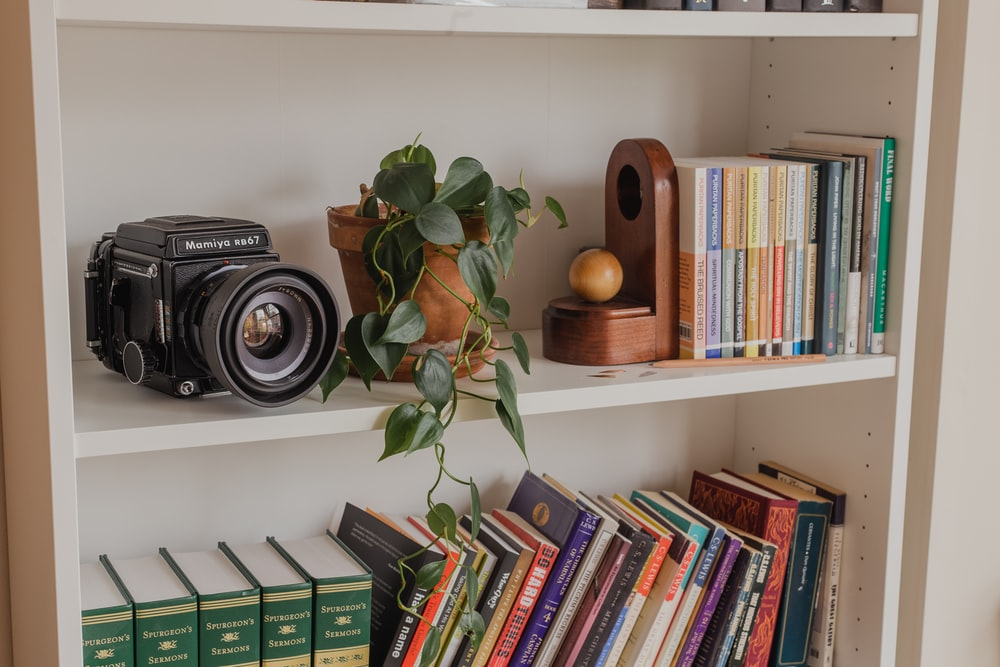 black and silver camera on white wooden shelf